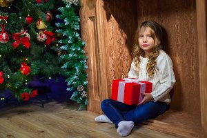 Merry Christmas happy girl with magic gift at home near Christma