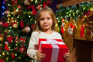 Little girl sitting by the tree holding a Christmas gift