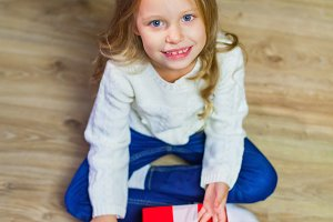 Happy little smiling girl with christmas gift box. View from abo