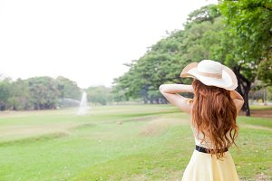 Woman with hat standing in the park.