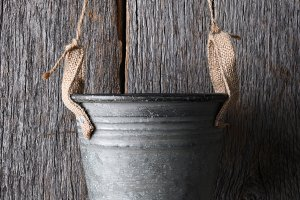 Empty bucket hanging against a wood