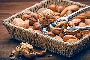 Walnut cracker sitting in basket full of nuts