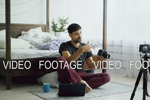 Handsome man photographer recording video blog about new camera sitting near bed at home