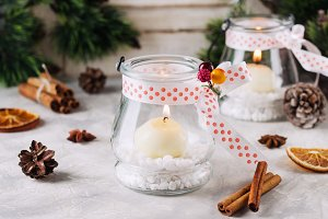 glass New Year candle holders with candles on a wooden white table, selective focus