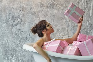 Girl sitting in the bath with gifts