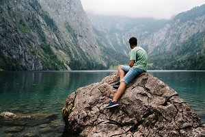 Young adult man sitting on rock looking at beautiful and misty l