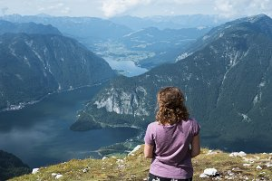 Beautiful young woman looking at the lake in the mountains