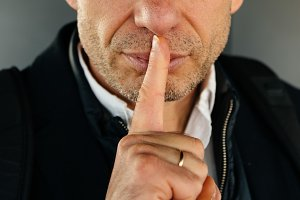 Attractive unshaved adult man with finger on lips making silence