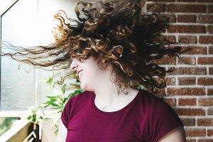 Beautiful teen girl shaking head with curly hair