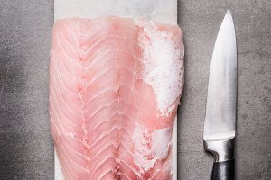 Raw fish fillet with knife