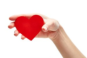 Red heart in woman hand isolated on white