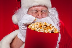 Close-up portrait Traditional Santa Claus watching TV, eating popcorn. Christmas. Red background. emotions. fear. surprise.