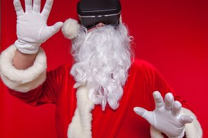 Santa Claus wearing virtual reality goggles, on a red background. Christmas