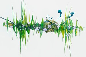 Headphones with a sound wave silhouette made from flowers and blades of grass