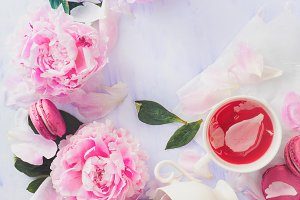 Flatlay with white coffee cup, macaroons and spilled pink peony flowers and petals