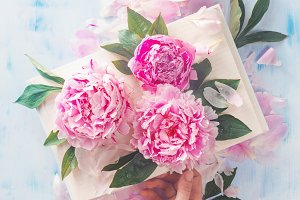 A hand holding an open book with pink peony flowers on a light wooden background