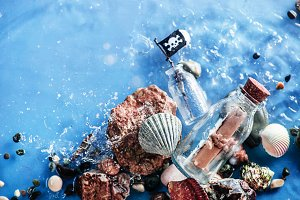 Message in a glass bottle on a pile of pebbles and seashells with a pirate flag