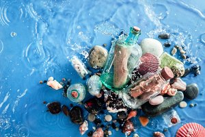 Two glass bottles with old paper notes on a water background with a ripple of seawave, seashells, pebbles, and sand