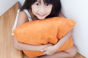 Girl sitting hugging pillow orange.