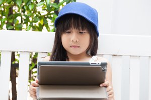 Girl playing with tablet on bench.
