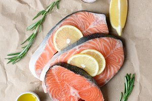 Salmon steaks, lemon, spices and herbs for cooking on paper background.
