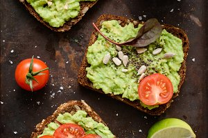 Useful avocado toasts with sprouts, tomato, seeds and sea salt flakes