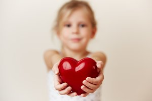 Child holding big red heart