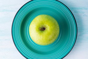 Green apple in ceramic dish