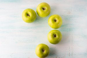 Green apples question mark on turquoise white table