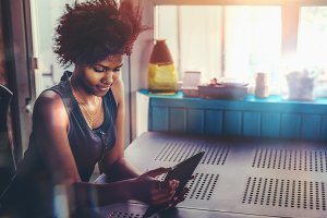 Black girl using tablet pc in room