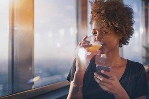 Girl with phone drinks orange juice