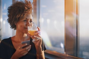 Black girl with juice and smartphone