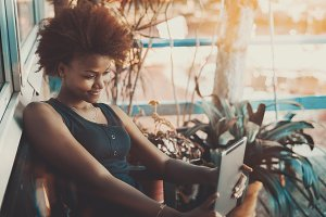 Curly black female with tablet pc