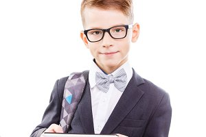 Cute schoolboy in glasses with tablet PC
