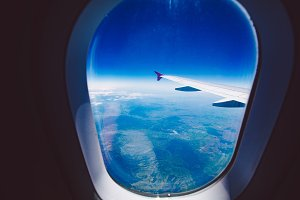 Looking through window aircraft during flight in wing blue sky