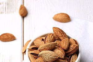 almonds in shell on a white wooden background