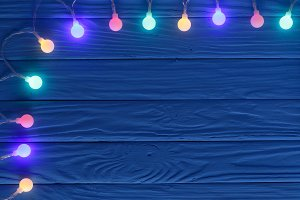 christmas garland lights on blue wooden background with copy space for your text. Top view