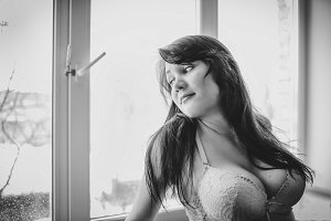 Seductive young busty woman in white lacy bra looking out the window.