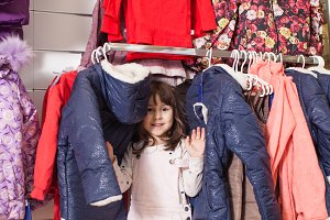 The little girl having fun in clothing store