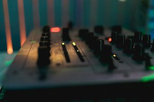 DJ control panel close-up. Blurred DJ mixer. Warm light. Background for a DJ's