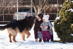 Mom with daughter and dog on winter walk