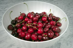 Ripe cherries in a white plastic bow