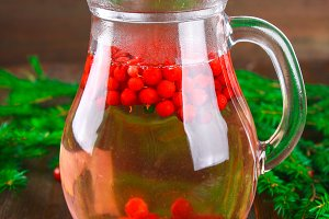 Morse or tea from cowberry in a glass jug surrounded by fir branches on a wooden table.