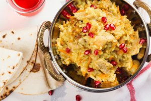 Pilaf with meat, spices and pomegranate seeds. Traditional dish of Asian cuisine