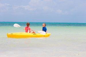 Little adorable girls enjoying kayaking on yellow kayak