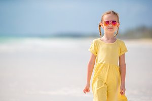 Active little girl on white beach. Closeup kid background the sea