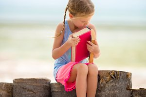Little adorable girl with book on tropical white beach
