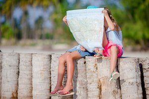Adorable little girls with big map of island on beach
