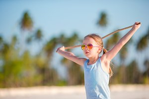Active little girl on white beach having fun. Closeup kid background the sea