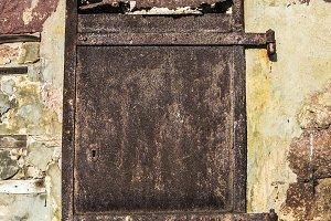 Old rusty door on a stone wall